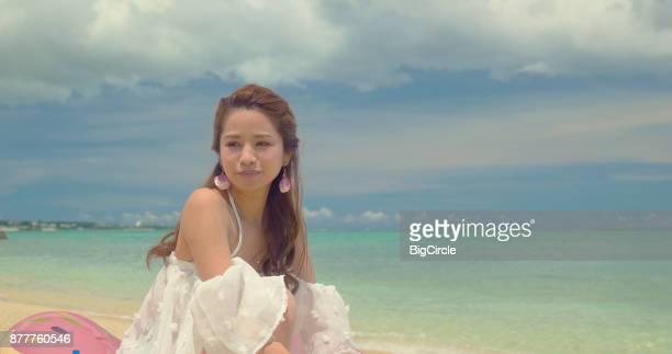 Japanese female sitting on the beach.