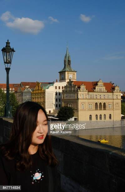 Japanese female tourist walks on the pedestrian Charles Bridge with the old city view in the background on July 18 2017 in Prague Czech Republic...