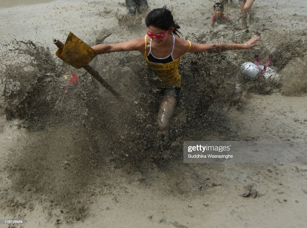 Japanese festival-goer runs to catch a flag during the village mud festival at Yumesaki on August 18, 2013 in Himeji, Japan. The festival has been held annually to encourage youths of the village to participate in the community.