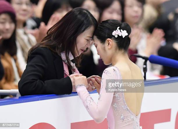 Japanese figure skater Satoko Miyahara shares a moment with her coach Mie Hamada before her short program performance at the NHK Trophy in Osaka on...