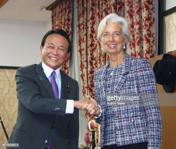 Japanese Finance Minister Taro Aso and International Monetary Fund Managing Director Christine Lagarde shake hands before starting talks in Tokyo on...