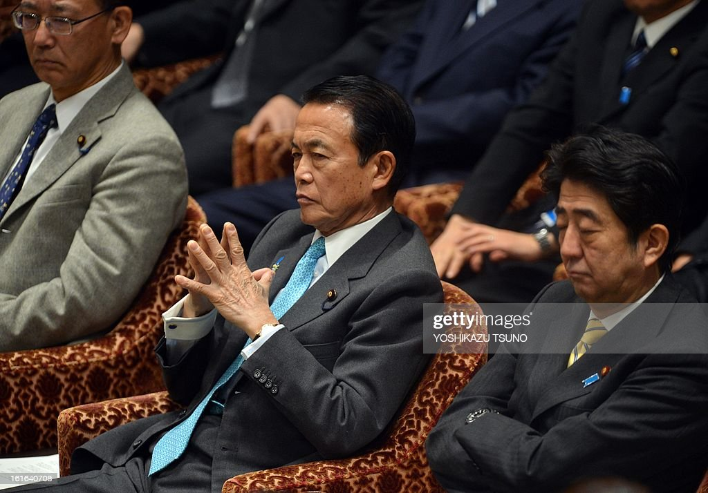 Japanese Finance Minister taro Aso (C) and Prime Minister Shinzo Abe (R) attend the Lower House's budget committee session at the National Diet in Tokyo on February 14, 2013. The governemnt and ruling coalition passed a 140 billion USD supplementary budget for the fiscal 2012 to finance economic stimulus. AFP PHOTO / Yoshikazu TSUNO