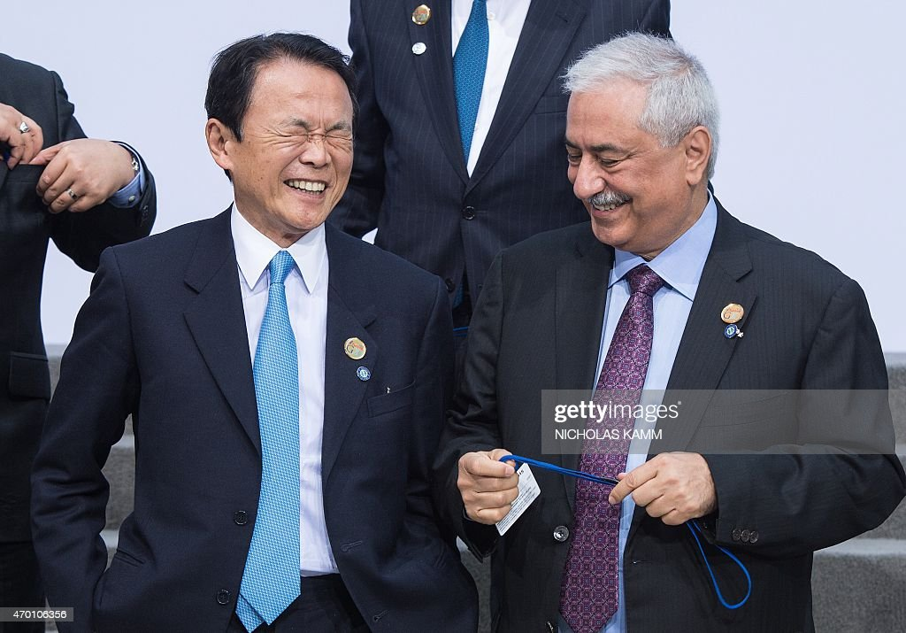 Japanese Finance Minister <a gi-track='captionPersonalityLinkClicked' href=/galleries/search?phrase=Taro+Aso&family=editorial&specificpeople=559212 ng-click='$event.stopPropagation()'>Taro Aso</a> (L) laughs with his Saudi counterpart Ibrahim Abdulaziz Al-Assaf as they arrive for the G20 family photo at the IMF/WB Spring Meetings in Washington, DC, on April 17, 2015.