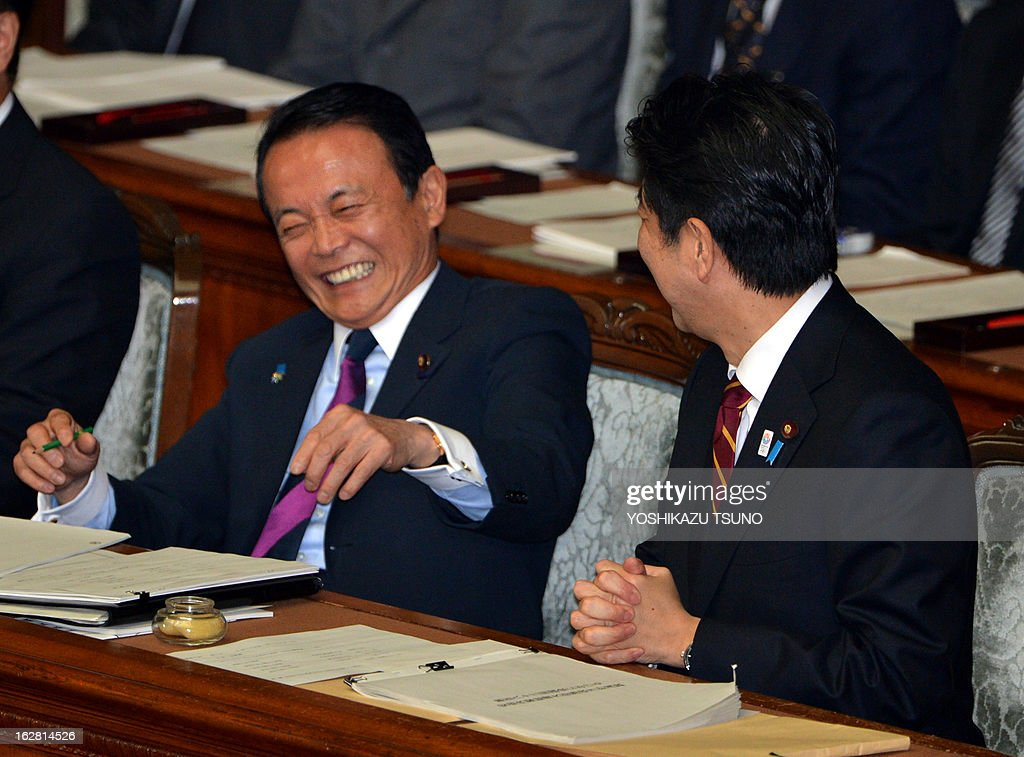 Japanese Finance Minister Taro Aso (L) makes a big laugh as he chats with Prime Minister Shinzo Abe before starting the Lower House's plenary session at the National Diet in Tokyo on February 28, 2013. Faced with a territorial dispute with China, Abe quoted former British prime minister Margaret Thatcher stressing the rule of law over the 1982 Falklands war. AFP PHOTO / Yoshikazu TSUNO