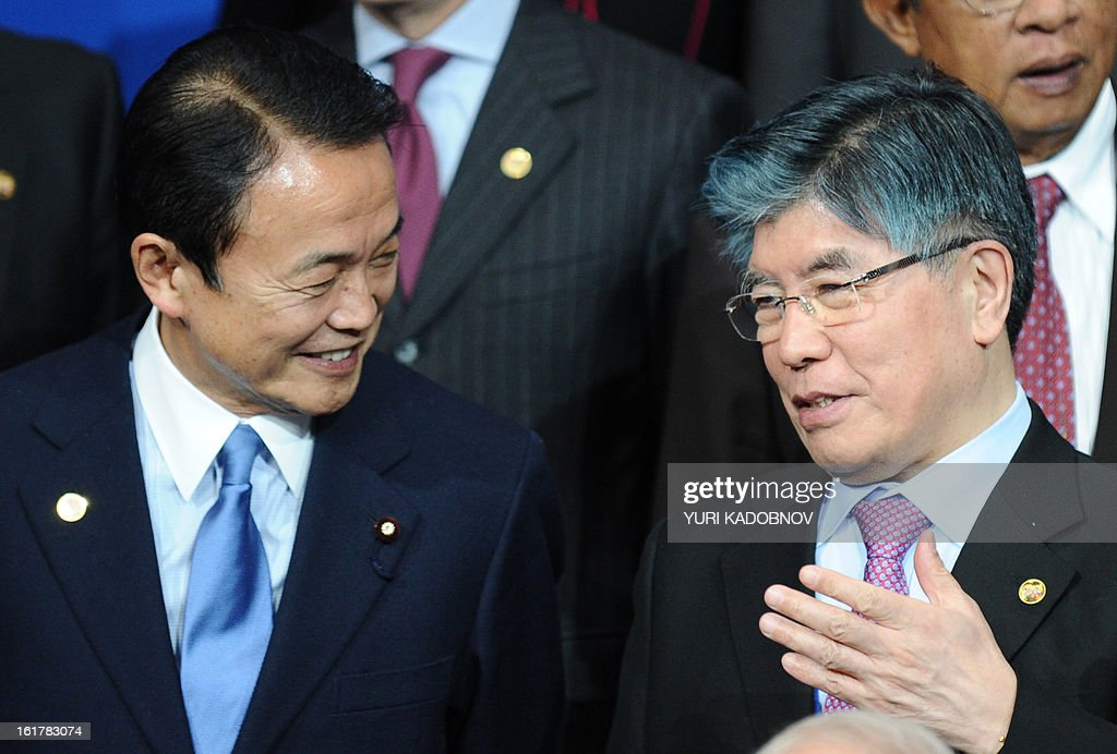 Japanese Finance Minister Taro Aso (L) speaks with Governor of Bank of Korea Kim Choongsoo (R) as they pose for family picture after a meeting of G20 states finance ministers and central bank governors in Moscow, on February 16, 2013. The ministers and central bank governors gathered today in Moscow for their first meeting in the Russian capital aimed at reassuring markets that the world's economic powers would not slug it out in 'currency wars' to boost national growth. AFP HOTO/YURI KADOBNOV