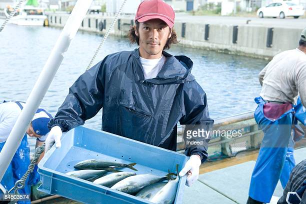 Japanese fisherman carrying crate of yellowtail