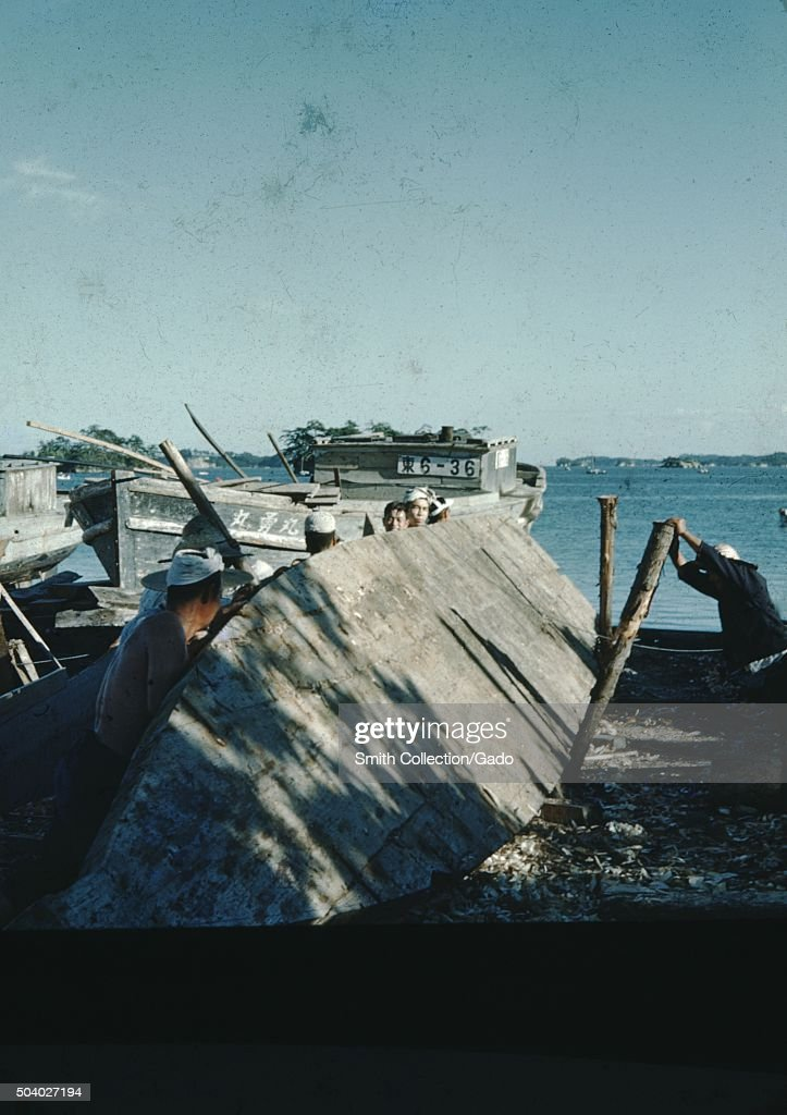 Japanese fishermen attempting to right the hull of a for Japanese fishing boat