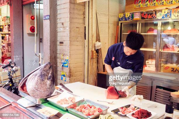 Japanese fishmonger cuts tuna as the first step in preparing sashimi Some of the freshest sashimi can be found in Tokyo's Tsukiji fish market the...