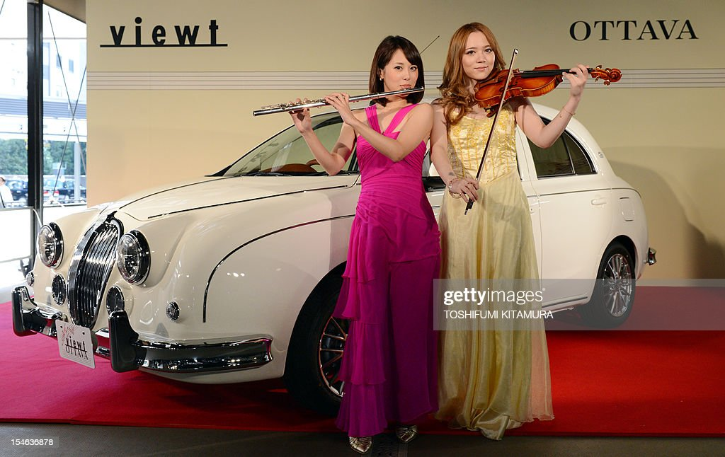 Japanese flutist Akiyo Ueta and violinist Asuka Ochi pose in front of Mitsuoka Motors' special edition 1200cc classic sedan car 'Viewt OTTAVA' during...