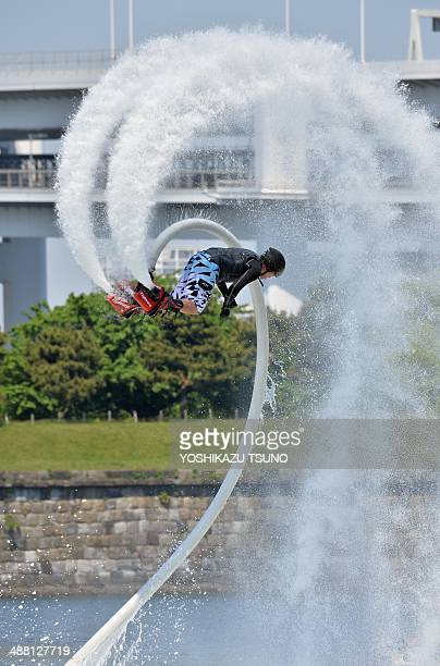 A Japanese flyboard rider performs with a waterpropelled flyboard which connects to a personal water craft with a hose during the Odaiba Beach Sports...