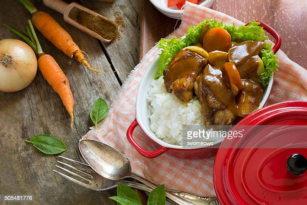 Japanese food curry rice with chicken on rustic wooden table top.