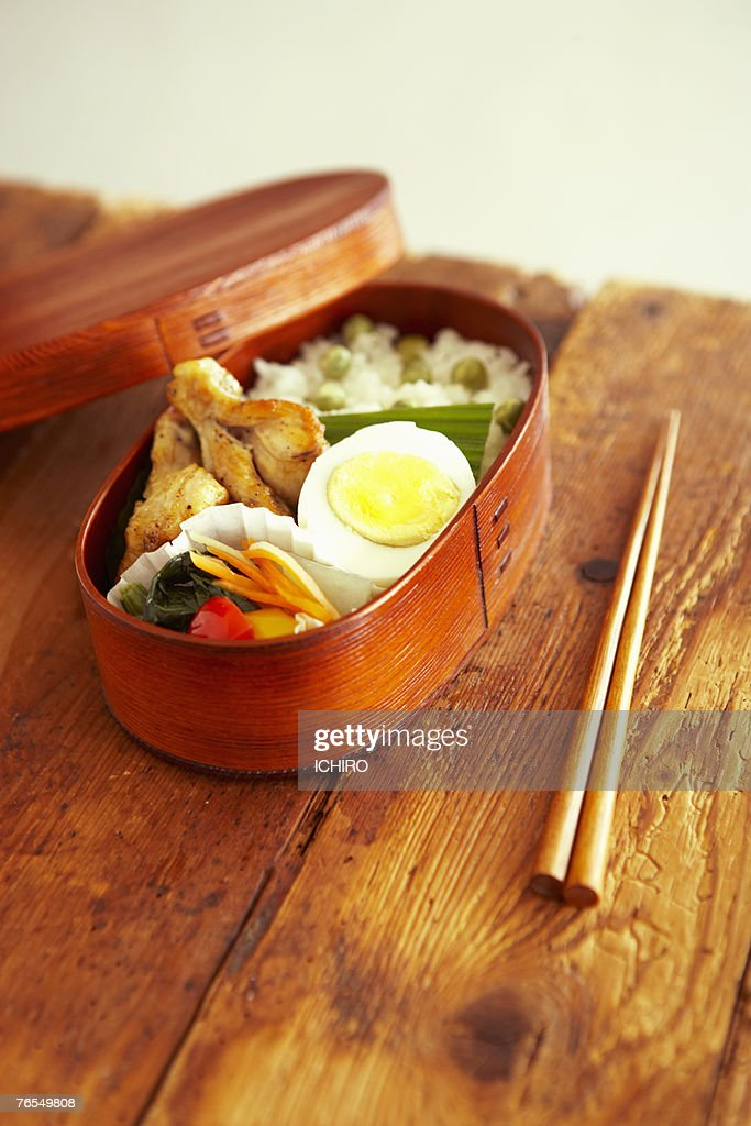Japanese food in wooden lunch box, next to chop sticks on wooden table