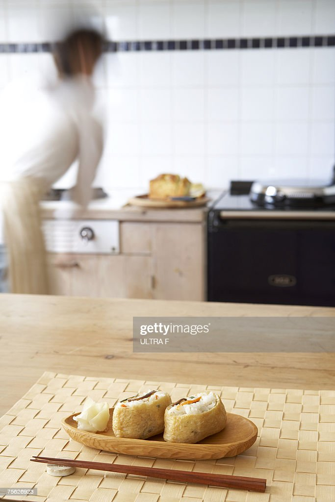 Japanese food on wooden tray with chopsticks on counter in kitchen, woman preparing food in background : Stock Photo