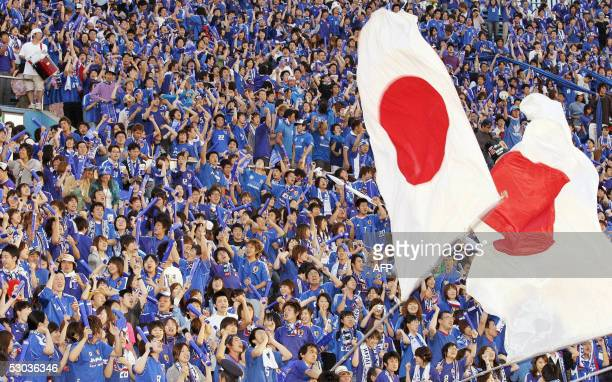 Japanese football supporters wave large flags and cheer Japan's national team players at the Japan's national stadium in Tokyo 08 June 2005 as they...