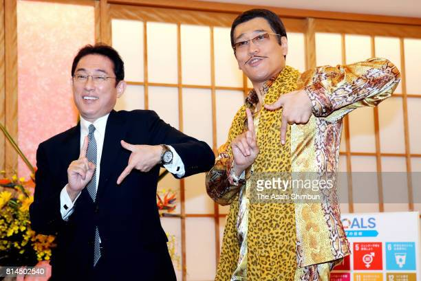 Japanese Foreign Minister Fumio Kishida and Pikotaro pose for photographs during their meeting at the Foreign Ministry on July 12 2017 in Tokyo Japan