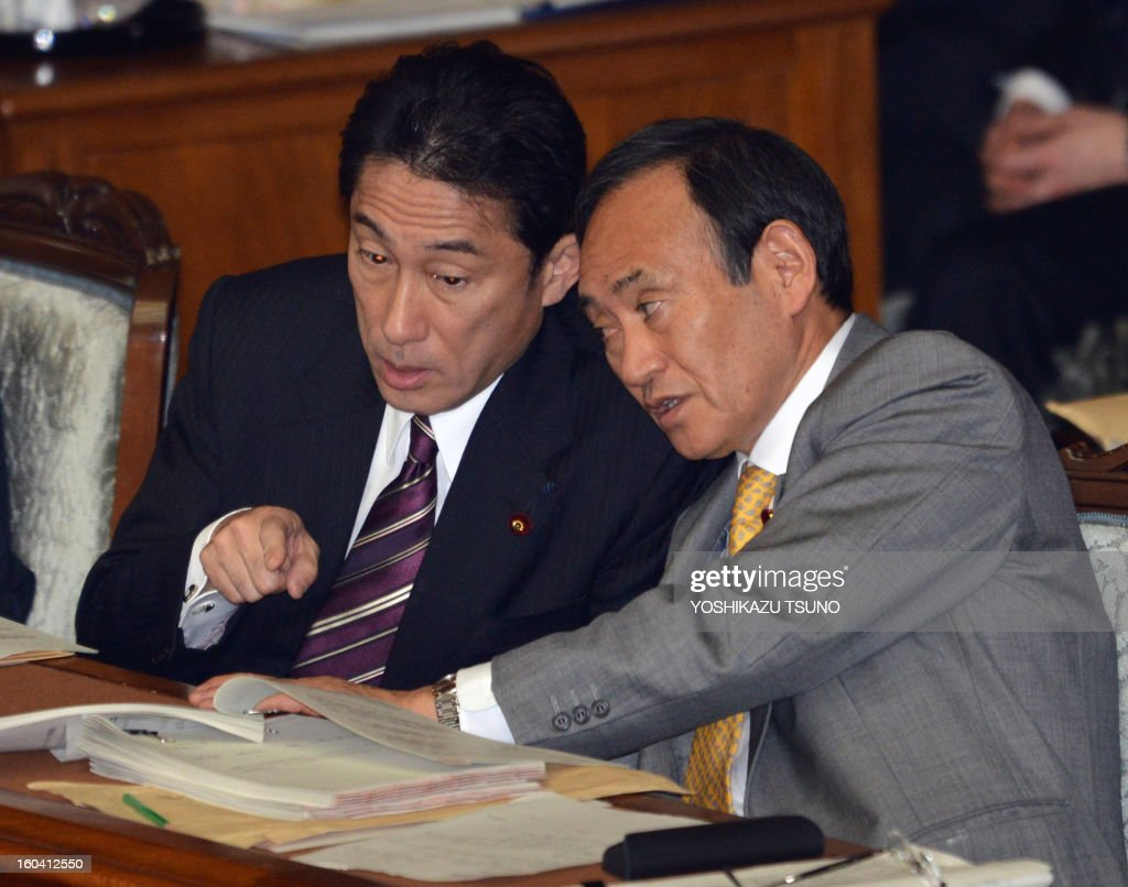 Japanese Foreign Minister Fumio Kishida (L) chats with Chief Cabinet Secretary Yoshihide Suga at the Lower House's plenary session at the National Diet in Tokyo on January 31, 2013. Japan's hawkish Prime Minister Shinzo Abe told parliament January 31 that he intends to change the country's post-World War II constitution, lowering the bar for further amendments. AFP PHOTO / Yoshikazu TSUNO