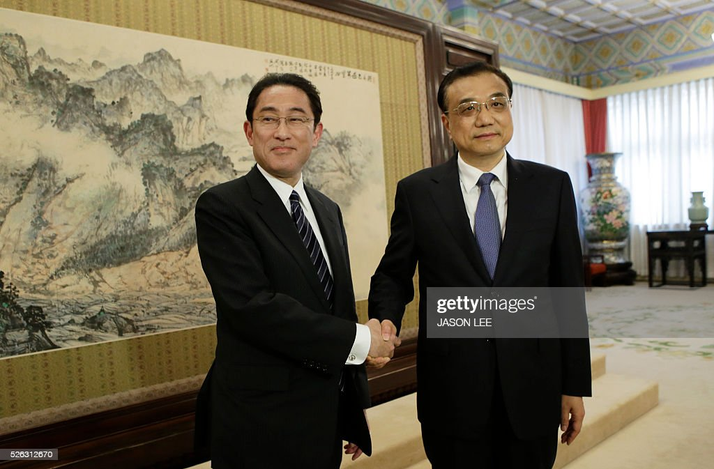 Japanese Foreign Minister Fumio Kishida (L) shakes hands with China's Premier Li Keqiang during a meeting at Zhongnanhai in Beijing on April 30, 2016. / AFP / pool / JASON LEE