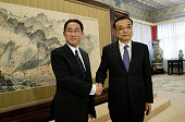 Japanese Foreign Minister Fumio Kishida shakes hands with China's Premier Li Keqiang during a meeting at Zhongnanhai in Beijing on April 30 2016 /...