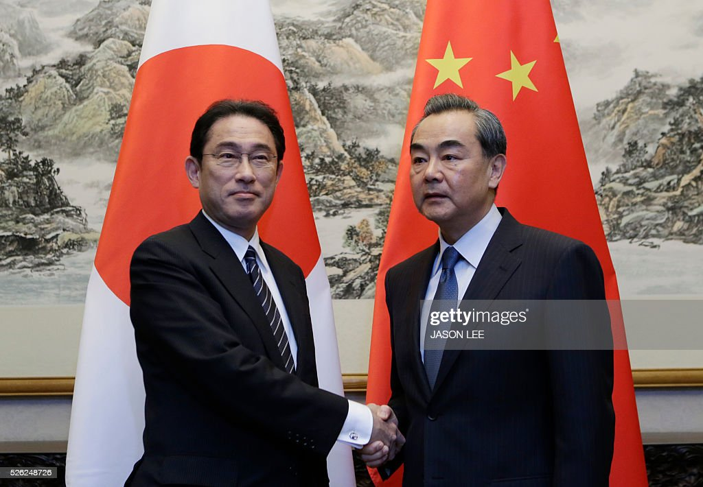 Japanese Foreign Minister Fumio Kishida (L) shakes hands with China's Foreign Minister Wang Yi during a meeting at Diaoyutai State Guesthouse in Beijing on April 30, 2016. / AFP / POOL / JASON LEE