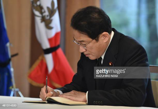 Japanese Foreign Minister Fumio Kishida writes a message in a condolence book at the French Ambassador to Japan Thierry Dana's residence in Tokyo on...