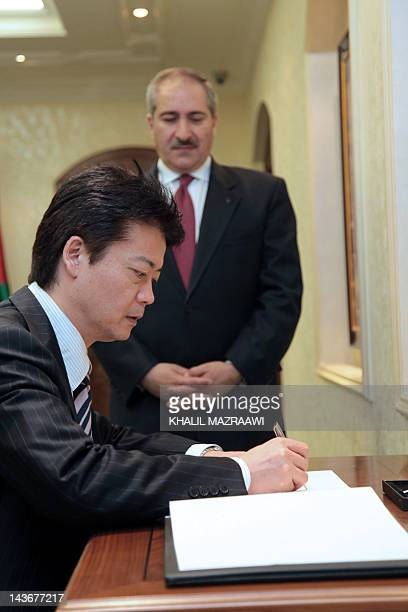 Japanese Foreign Minister Koichiro Gemba signs the guest book at the foreign ministry during a meeting with his Jordanian counterpart Nasser Judeh in...