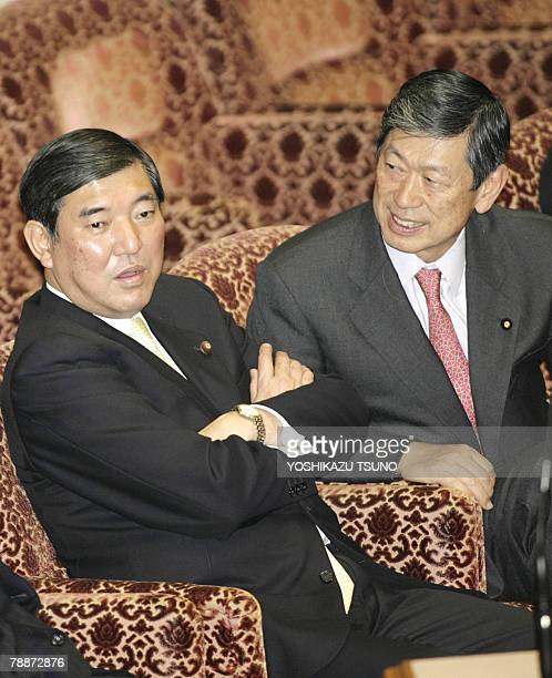 Japanese Foreign Minister Masahiko Komura chats with Defence Minister Shigeru Ishiba during the Upper House's committee session to resume a disputed...