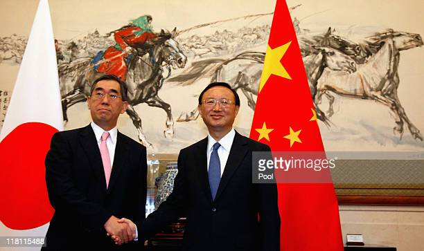 Japanese foreign minister Takeaki Matsumoto shakes hands with Chinese foreign minister Yang Jiechi at the Diaoyutai State guesthouse on July 4 2011...