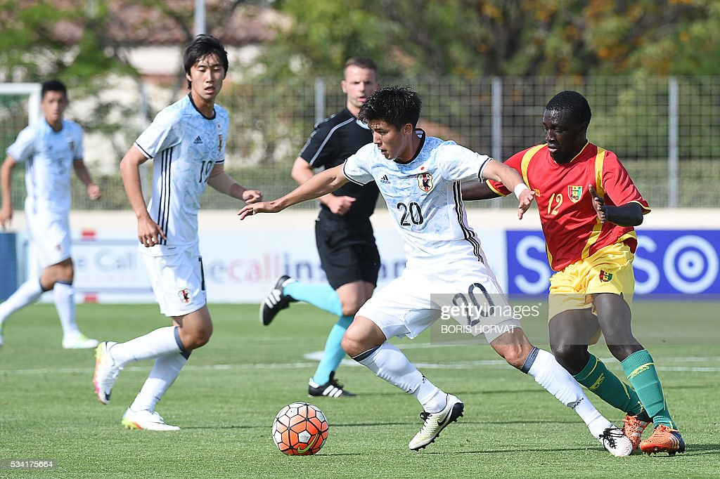 Japanese forward Cayman Togashi (C) vies with Guinean defender Seiti Toure (R) during the Under 21 international football match between Japon and Guinea, at the Antoine Baptiste stadium in Six-Fours, southern France on May 25, 2016, as part of the Tournoi Espoirs de Toulon (Toulon Hopefuls' Tournament). / AFP / BORIS