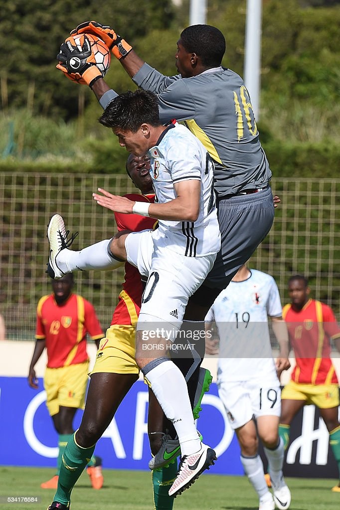 Japanese forward Cayman Togashi (L) vies with Guinean goalkeeper Ousmane Doucoure (R) during the Under 21 international football match between Japon and Guinea, at the Antoine Baptiste stadium in Six-Fours, southern France on May 25, 2016, as part of the Tournoi Espoirs de Toulon (Toulon Hopefuls' Tournament). / AFP / BORIS