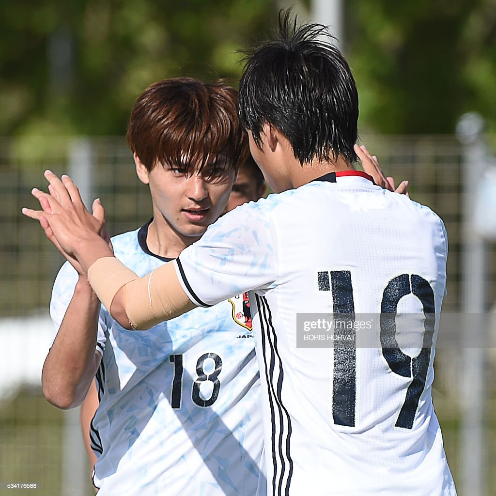 Japanese forward Takumi Minamino (L) celebrates with Daichi Kamada (R) after scoring, during the Under 21 international football match between Japon and Guinea, at the Antoine Baptiste stadium in Six-Fours, southern France on May 25, 2016, as part of the Tournoi Espoirs de Toulon (Toulon Hopefuls' Tournament). / AFP / BORIS