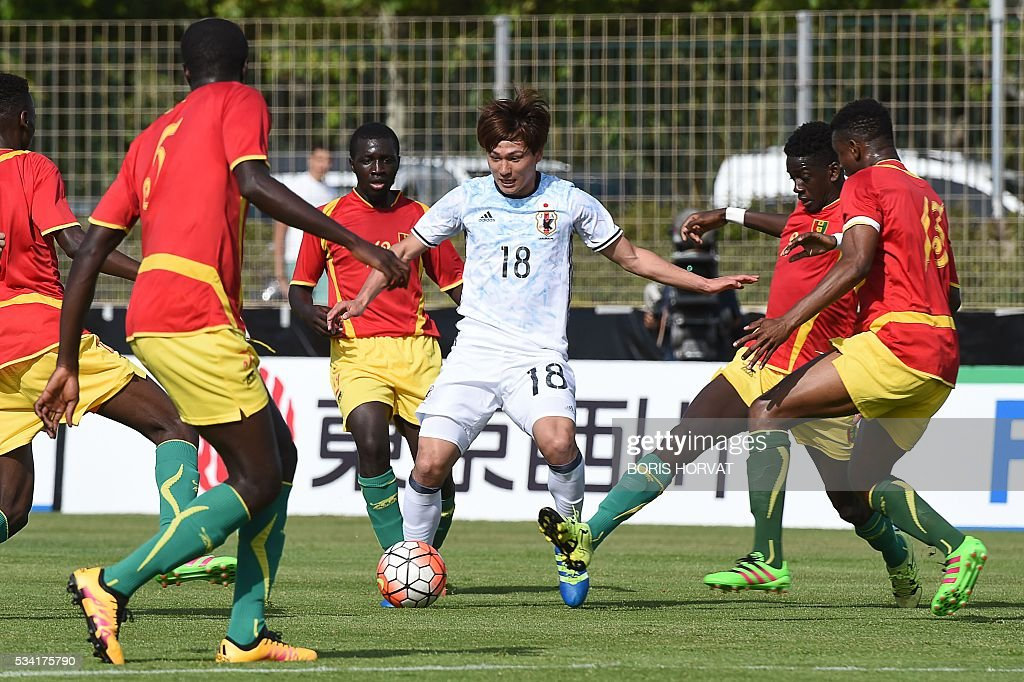Japanese forward Takumi Minamino (C) vies with Guinean defender Mohamed Toure (L) and Abdouley Cisse (R) during the Under 21 international football match between Japon and Guinea, at the Antoine Baptiste stadium in Six-Fours, southern France on May 25, 2016, as part of the Tournoi Espoirs de Toulon (Toulon Hopefuls' Tournament). / AFP / BORIS