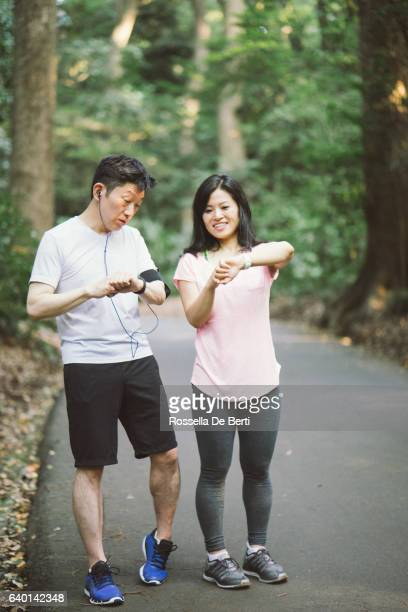 Japanese friends checking data on smartphone while doing sport outdoors