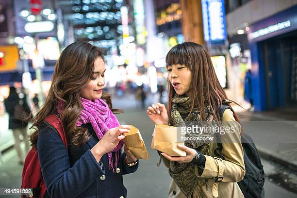 japanese friends eating a snack on the night in tokyo
