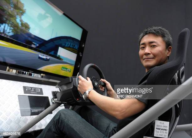 Japanese game designer and creator of the video game 'Gran Turismo' Kazunori Yamauchi poses playing 'Gran Turismo' where the virtual 'Vision Gran...