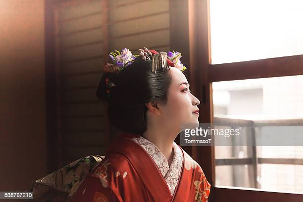Japanese Geisha looking through the window
