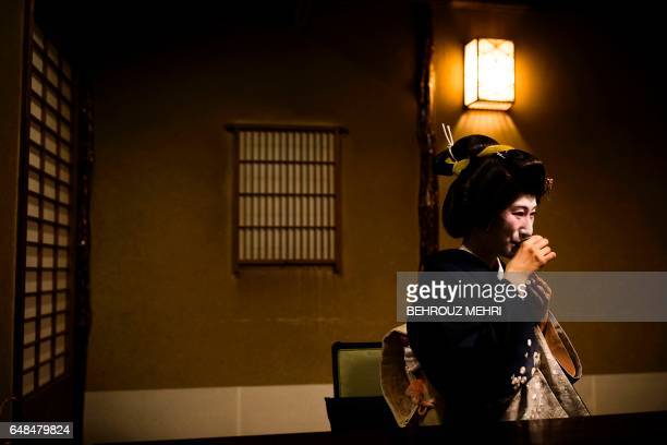 Japanese Geisha Natsuki drinks sake with her guests from the US at a traditional restaurant in Tokyo on November 14 2016 Adorned in crisp kimonos...