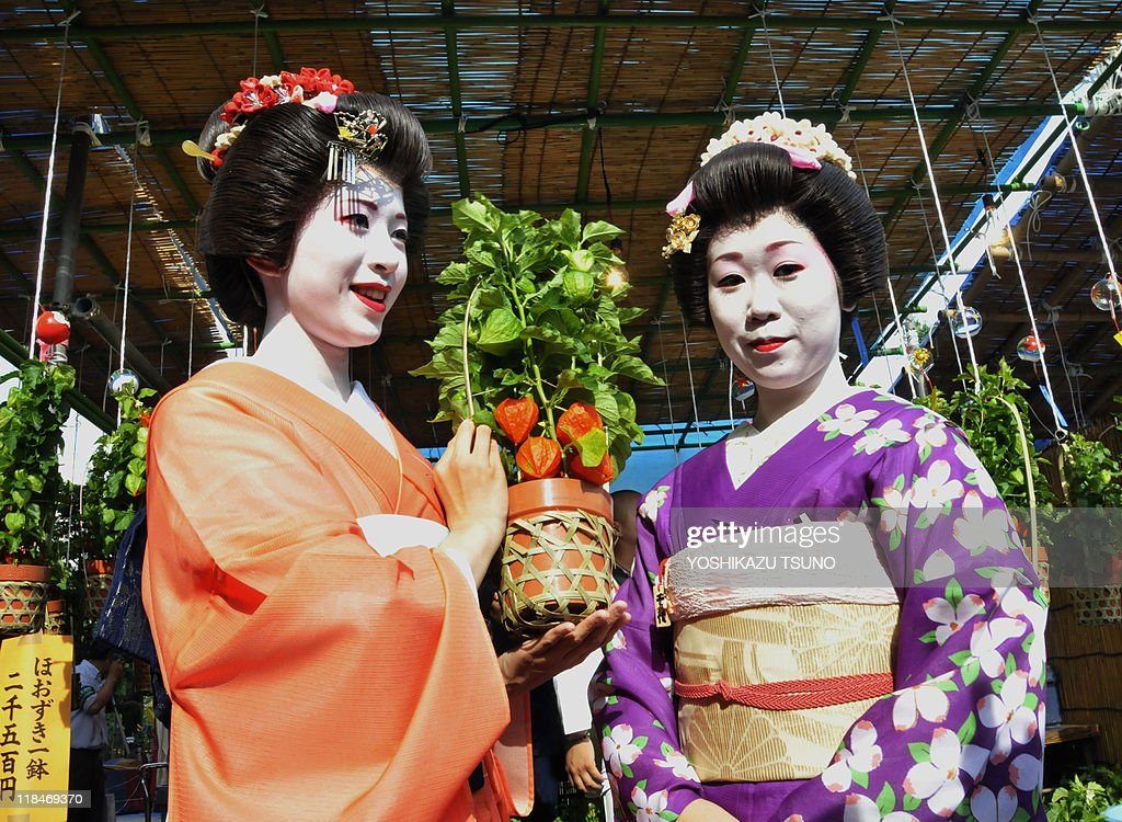 Japanese geisha Yanagi (L) and Chiyo hold a pot of 'hozuki' or Chinese lantern plant at Tokyo's Sensoji temple on July 8, 2010 at the preview for the promotion of the annual two-day Chinese lantern plant fair held July 9-10. The plants are considered part of early summer's poetic scenery in Japan and some 500,000 people are expected to visit the fair. AFP PHOTO/Yoshikazu TSUNO