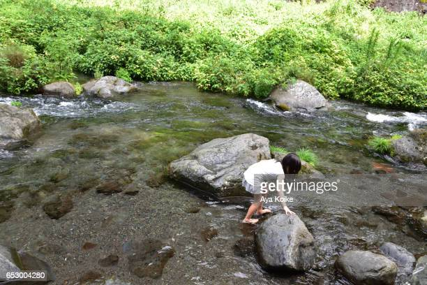 A Japanese girl, 7 years old, playing in the summer river
