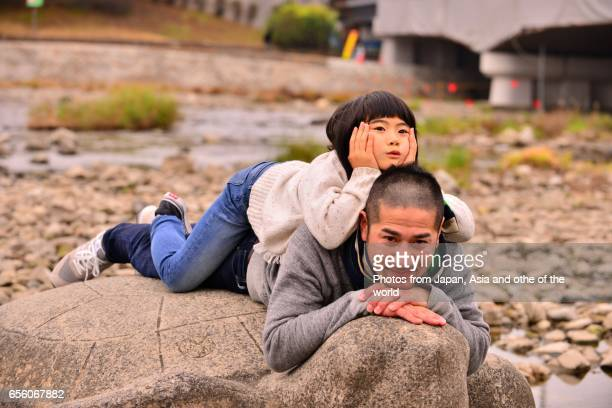 Japanese Girl and Her Father Relaxing by Kamo River, Kyoto