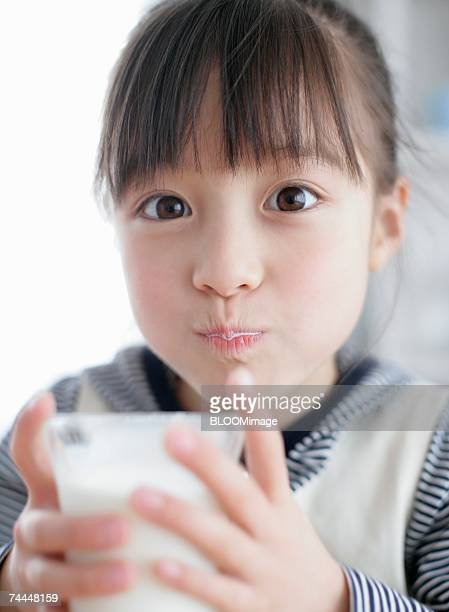 Japanese girl drinking milk with looking at camera