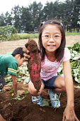 Japanese girl holding sweet potato, smiling