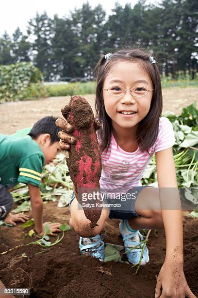 Japanese girl holding sweet potato, smiling