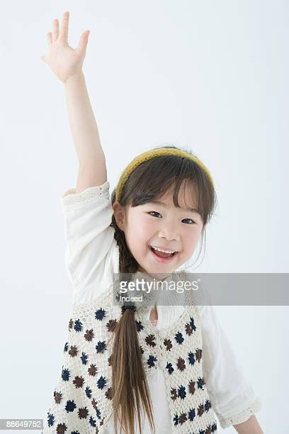 Japanese girl (6-7 years) raising hand, smiling