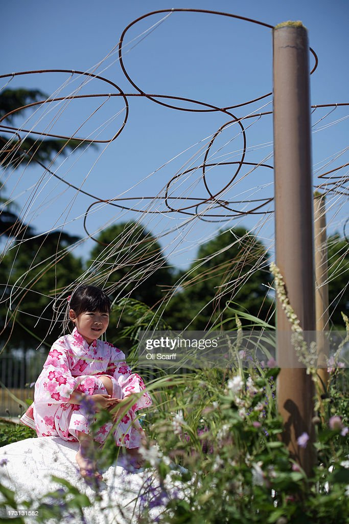A Japanese girl sits in the 'Spirit of the Land' garden at the Hampton Court Palace Flower Show on July 8, 2013 in London, England. Hampton Court Palace Flower Show opens to the public tomorrow and runs until July 14, 2013. It is the world's largest flower show with over 600 exhibitors spread over 34 acres.