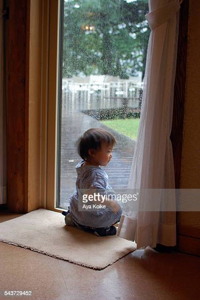 A Japanese girl sitting near the window, looking at the rain