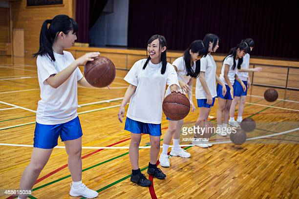 Japanese girls practising basketball in the school gymnasium