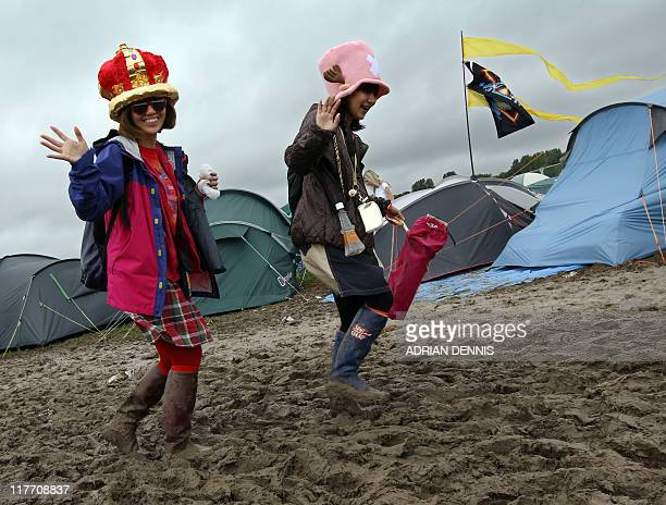Japanese girls walk along a muddy path on their way to the stages during the Glastonbury festival near Glastonbury Somerset on June 25 2011 Now in...