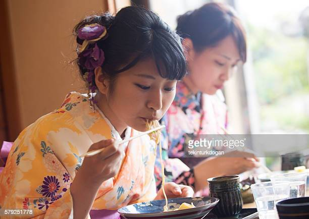 japanese girls with kimono costume eating noodle at kyoto japan