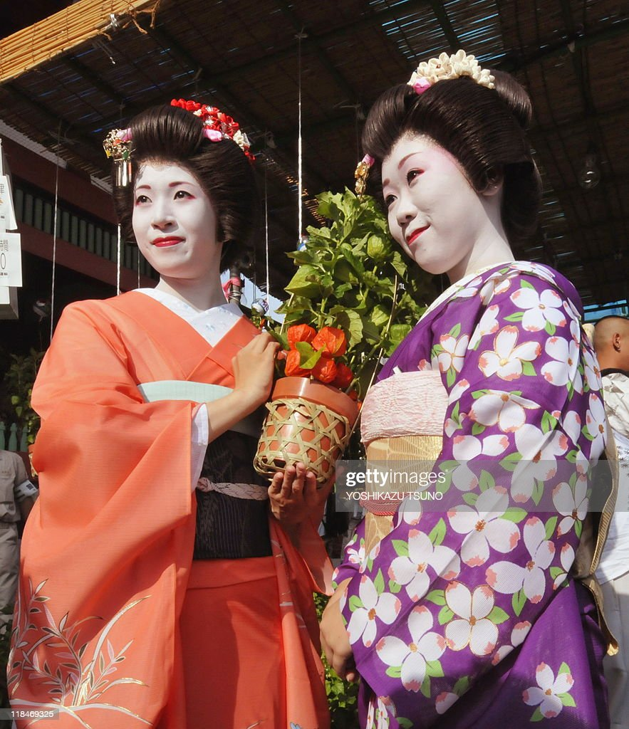 Japanese girls Yanagi (L) and Chiyo hold a pot of 'hozuki' or Chinese lantern plant at Tokyo's Sensoji temple on July 8, 2010 at the preview for the promotion of the annual two-day Chinese lantern plant fair held July 9-10. The plants are considered part of early summer's poetic scenery in Japan and some 500,000 people are expected to visit the fair. AFP PHOTO/Yoshikazu TSUNO