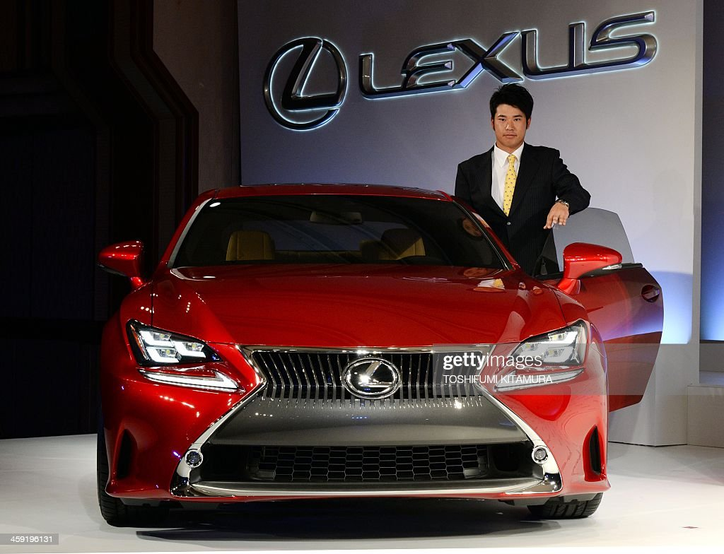 Japanese golfer Hideki Matsuyama stands beside a Lexus sports coupe, RC during a press conference on his sponsorship with Lexus in Tokyo on December 24, 2013. 21-year-old Matsuyama, the first rookie golfer to top the winnings list on the Japan Golf Tour, signed a three-year sponsorship with Lexus.